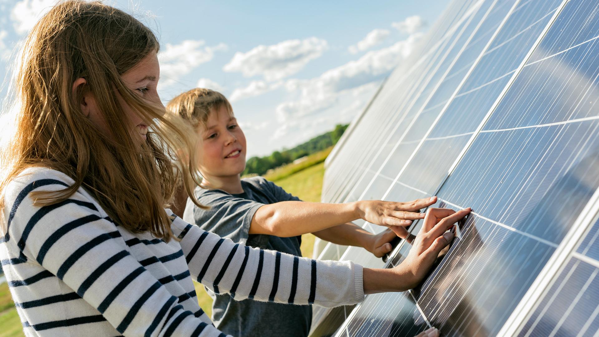 En pojke och en flicka som rör vid solpaneler
