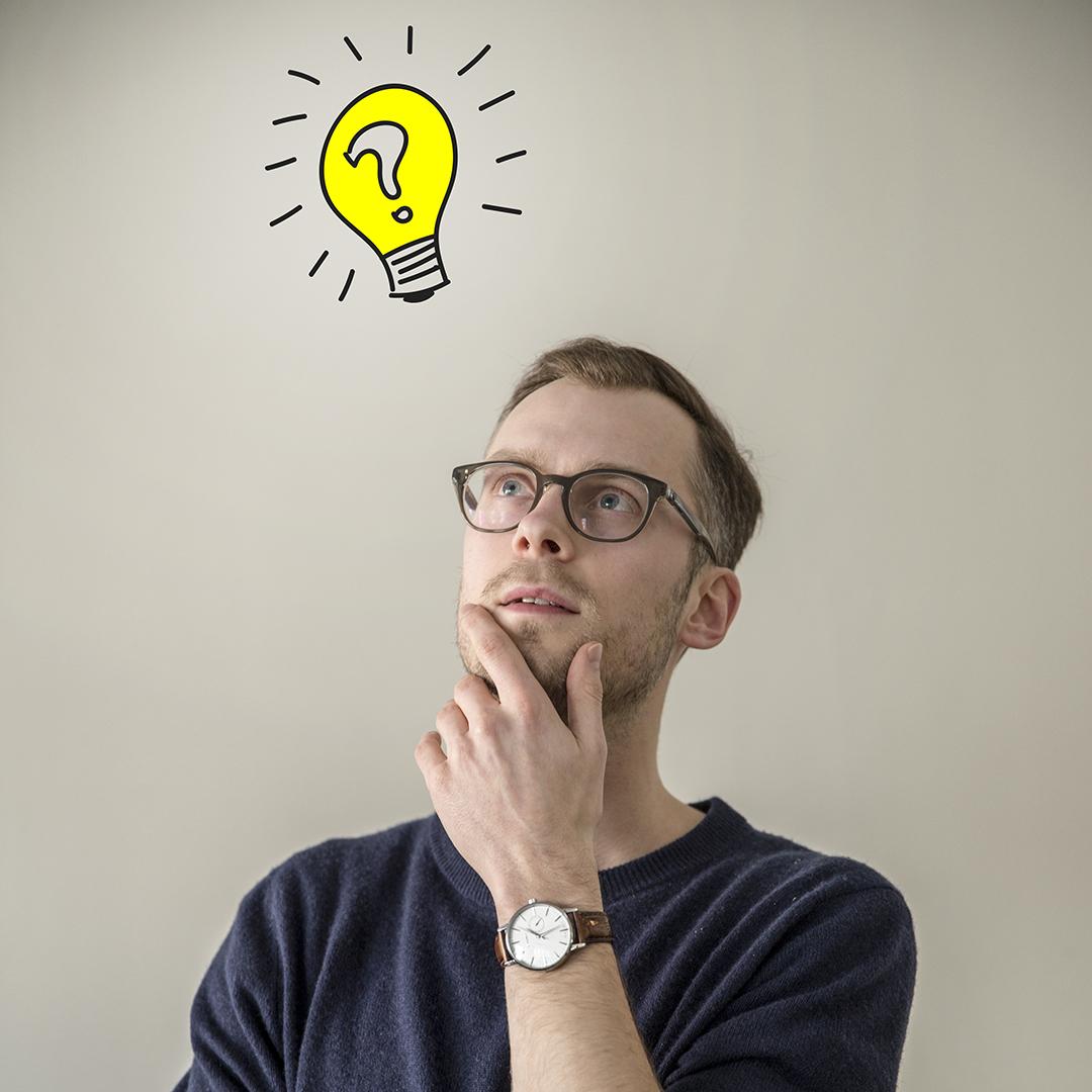 Man som ser ut att tänka, en tecknad glödlampa indikerar att han får en idé