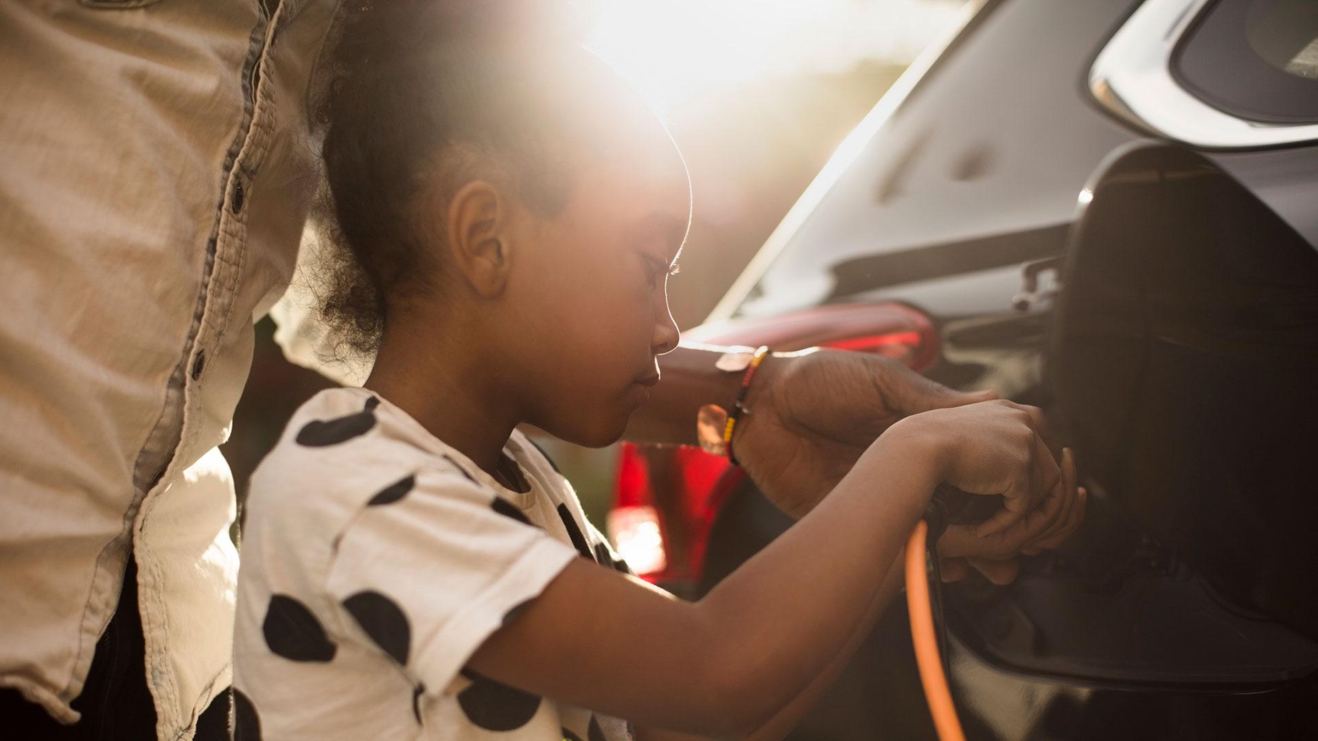 Ung flicka som hjälper sin pappa ladda deras elbil.