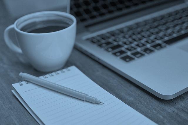 Kaffekopp, laptop och anteckningsblock