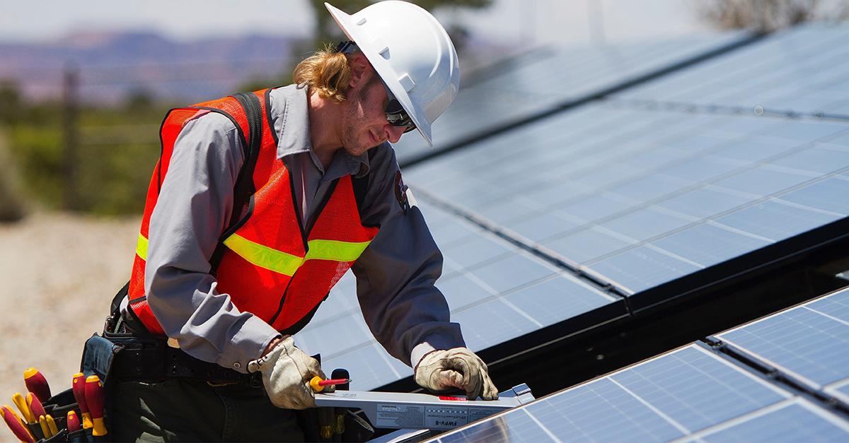 Man som installerar solcellspaneler
