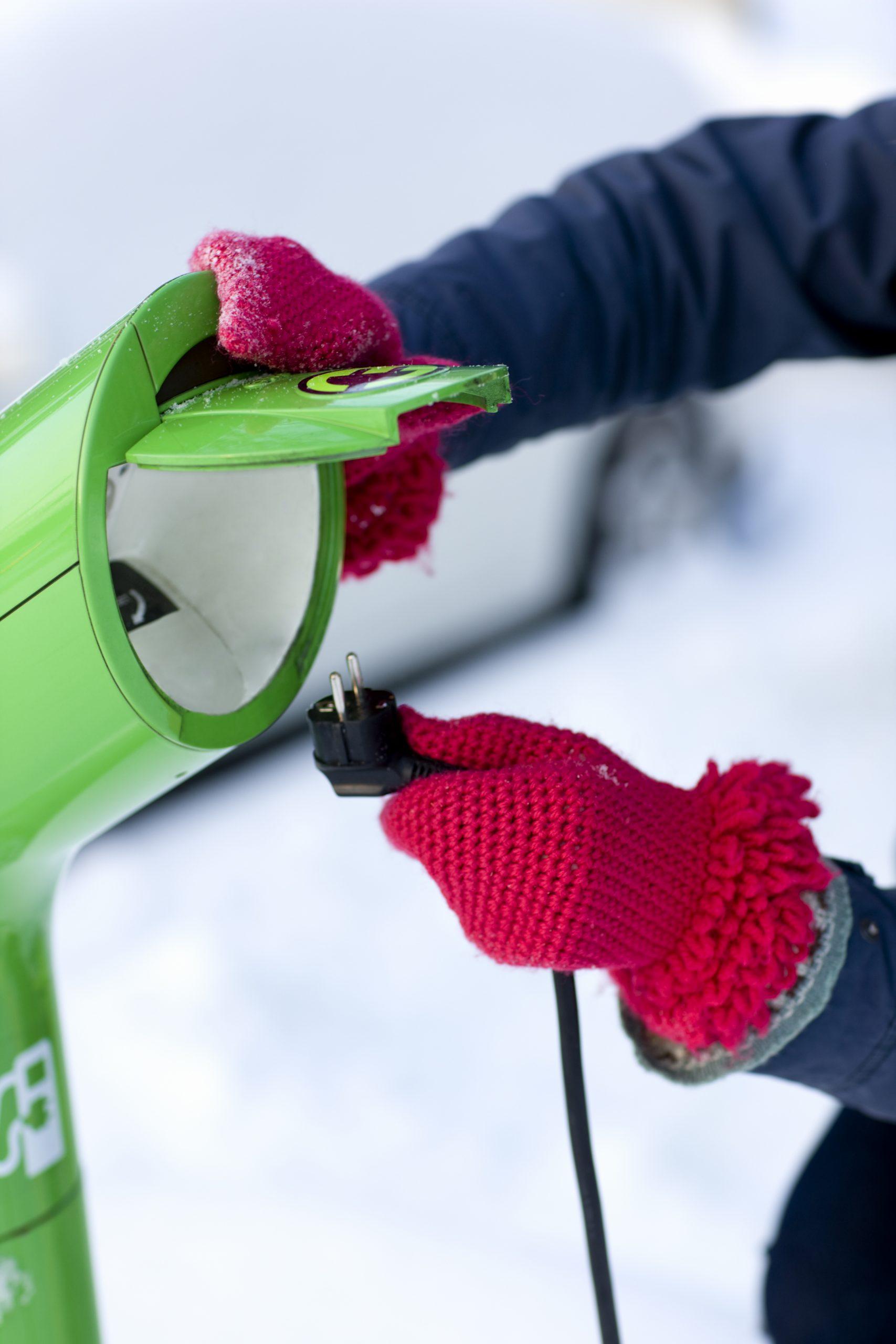 Person är på väg att sätta i en kontakt i en laddstolpe. Det är vinter och snö, personen har röda tumvantar.
