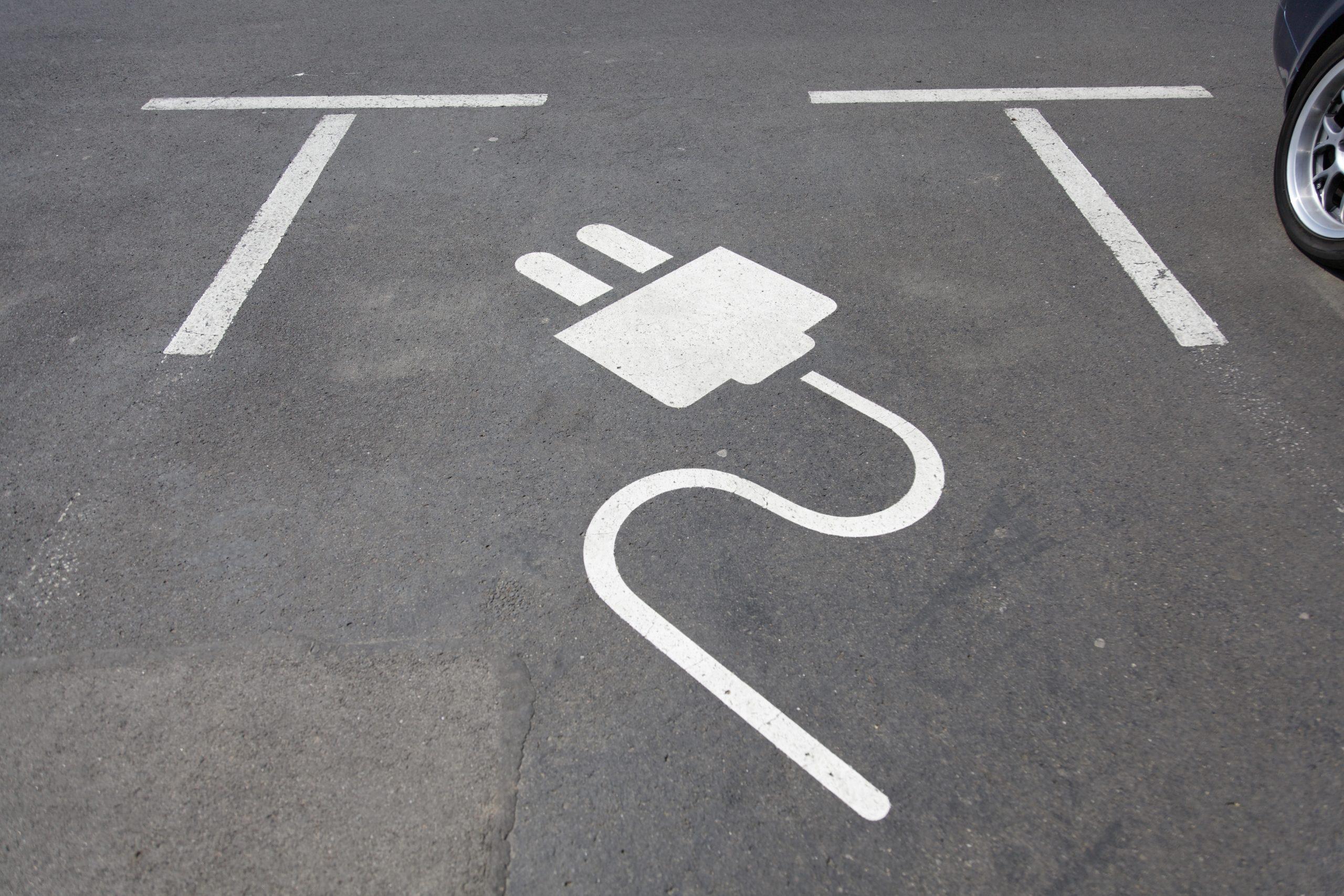 Parkeringsplats med en målad ladd kontakt, en symbol som indikerar laddning